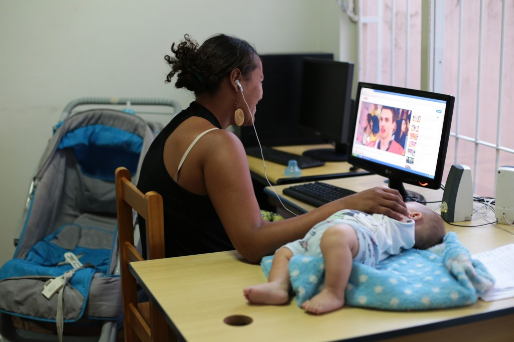 Natália utiliza o computador do abrigo, enquanto cuida de seu filho no Abrigo Feminino Casa Santa Clara, ligado à Cáritas   (Fotos: Adriano Rosa)