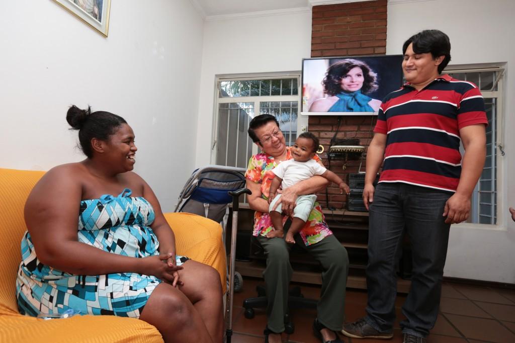A ex-moradora de rua Priscila, na sala de TV, conversa com Terezinha Shibuta, diretora voluntária do Abrigo Feminino Santa Clara (que segura o filho de Priscila), e o coordenador do abrigo, Roberto Naiber Willis Torrico (Fotos: Adriano Rosa)
