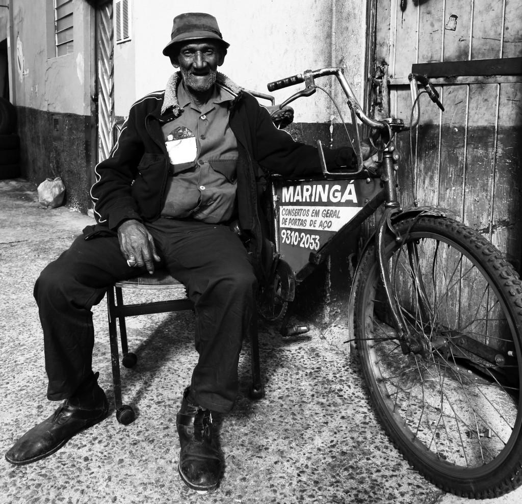 Onofre da Silva Marques: O Maringá, como é popularmente conhecido no centro da cidade, é o cara encarregado de engraxar e concertar as portas de aço das lojas de muitas das lojas da 13 de Maio. Isso desde os anos 50. Quando era mais jovem, o serviço dele também era de apagar as luzes das vitrines depois das 22hs. Na foto com sua inseparável antiquíssima bicicleta, onde carrega suas ferramentas (Foto Adriano Rosa)