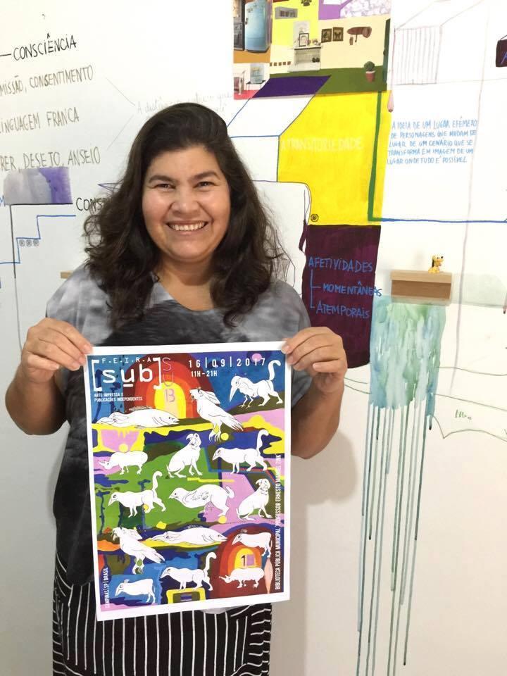 Valéria Menezes e o cartaz que concebeu para a Feira SUB 2017 (Foto Divulgação)