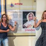 Synnöve e a também artista plástica Rosana Amorim, no cartaz com informações e a foto da homenageada neste ano na mostra Batom, Lápis e Humor (Foto Divulgação)